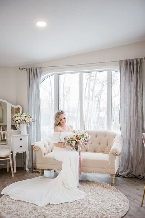 Bride in getting ready suite sitting on a sofa holding a pink and white bridal bouquet with trailing ribbons