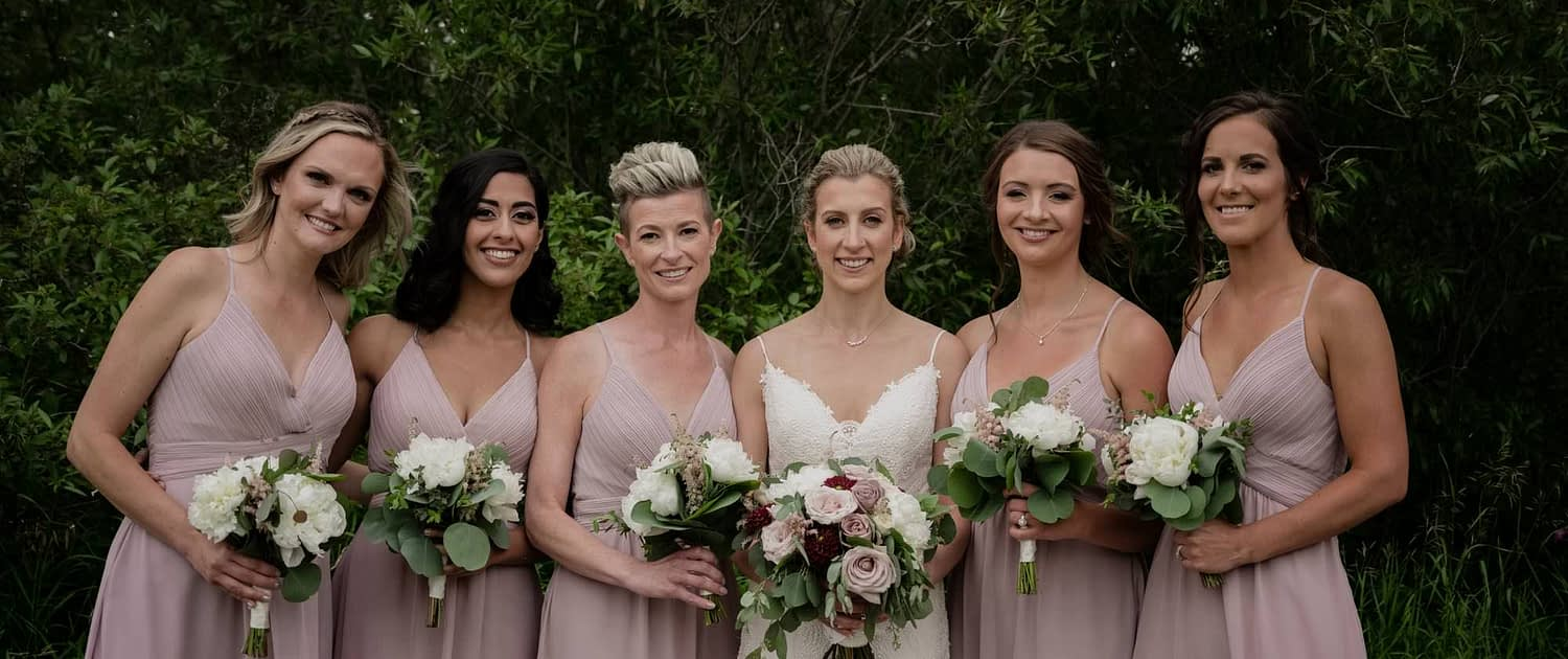 Burgundy and Mauve bride and bridesmaids; bridesmaids wearing mauve dresses and carrying white and blush bouquets designed with astilbe, peonies and eucalyptus; bride carrying white, blush, mauve and burgundy bouquet designed with dahlias, quicksand roses, ranunculus, peonies, amnesia roses, astilbe and eucalyptus