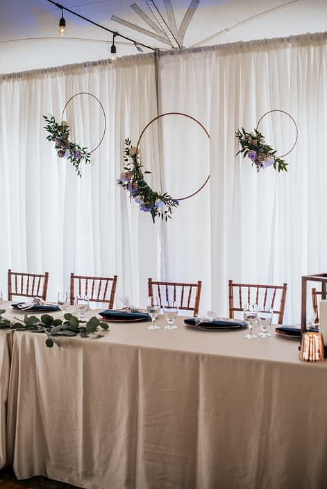 Erin and Nick's Mauve and Navy Winter Wedding head table decorated with copper hoops accented by flowers