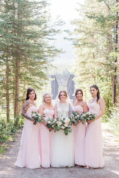 Amy and her bridesmaids carrying pink and blue bouquets featuring white o'hara garden roses, quicksand roses, ranunculus, astilbe, delphinium, eryngium and eucalyptus. The bridesmaids are wearing pink floor length dresses and the bride is wearing a white embroidered bridal gown.