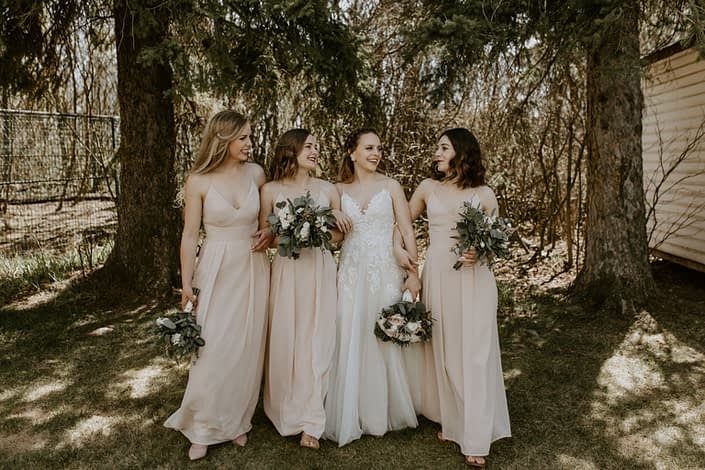 Bride with bridesmaids wearing blush floor length dresses and holding blush, white and burgundy bouquets