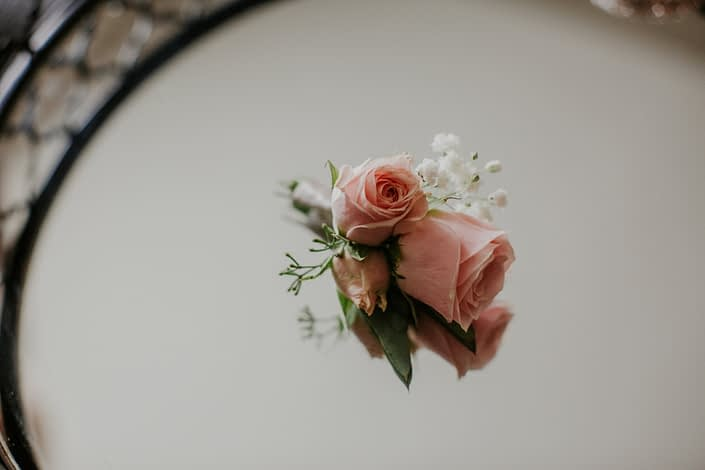 small spray rose boutonniere designd with blush spray roses and white babies breath and eucalytpus in a mirror