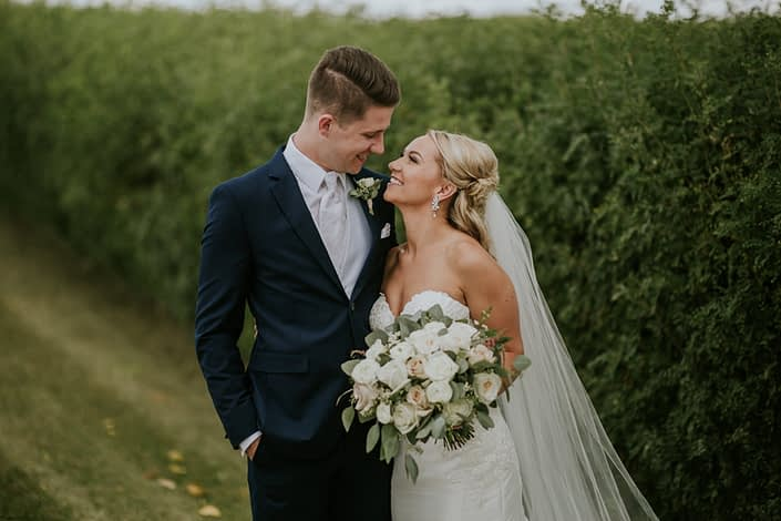 Brooke and Levi smiling at each other while holding a blush and ivory bouquet made of white o'hara garden roses, quicksand roses, playa blanca roses, astilbe, waxflower and eucalyptus greenery.