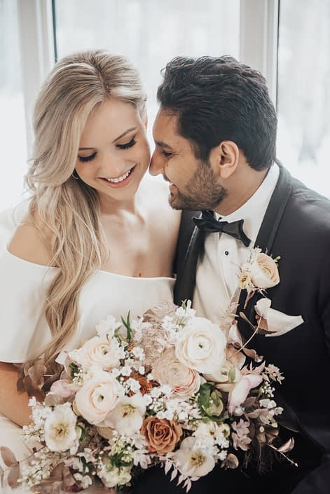 Planning Your Wedding Flowers with Calyx Floral Design: Everything You Need to Know; bride and groom with blush pink, white and rose gold bridal bouquet and boutonniere; roses, ranunculus, hellebores, plumosa, iltalian ruscus, plumosa
