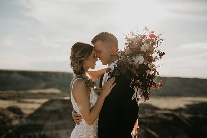 bride and groom at sunset with a brdal bouquet designed with white scabiosa, quicksand roses and burgundy greenery