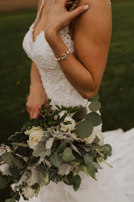 White and grey green bridal bouquet with a vintage feel designed with playa blanca roses, lisianthus, astilbe, blue star succulents, dusty miller and eucalyptus.