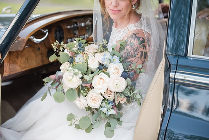 Amy in a vintage car holding her pink and blue bridal bouquet featuring white o'hara garden roses, quicksand roses, pale pink ranunculus, astilbe, blue delphinium, eryngium, and eucalyptus.