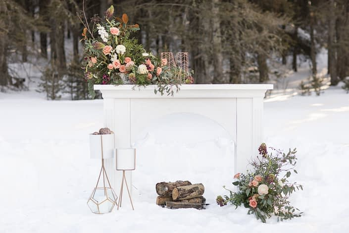 Elegant White Winter Wedding Styled Shoot - White mantle with gold geometric decorations with floral arrangements designed in each, blush and burgundy in winter