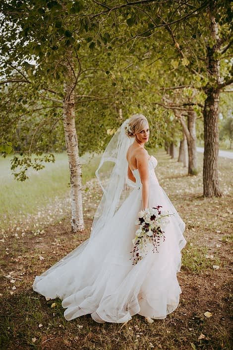 bride in the trees in a summer wedding with a veil holding a bouquet of white calla lilies and white dendrobium orchids and burgundy dendrobium orchids