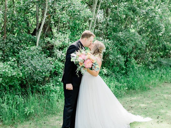 Talyor and Griffin kissing while holding a bouquet made of coral charm peony, yellow roses, monstera leaf, boston fern, and eucalyptus greenery.