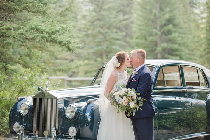 Amy and Kerry kissing in front of a vintage car. Amy is holding a pink and blue bridal bouquet made of white o'hara garden roses, quicksand roses, ranunculus, delphinium, astilbe, eryngium, and eucalyptus. Kerry is wearing a boutonniere made of white spray roses, blue delphinium, astilbe, eryngium and eucaluptus.