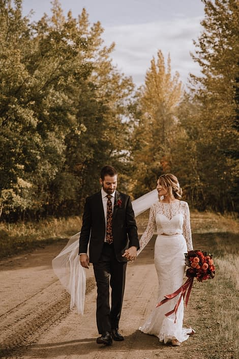 Bride in long sleeved dress with long veil with groom in floral tie walking down a dirt road in the woods with a bouquet with trailing ribbons and orange dahlias and black bacarra roses and burgundy anthuriums and magnolia leaves