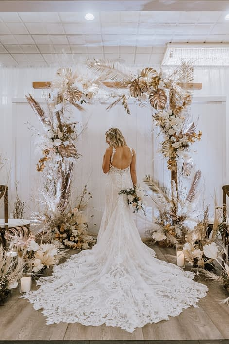 Model wearing lace gown and holding a bouquet made of blush and white playa blanca roses, sweet peas and eucalyptus standing under a wooden archway decorated with Pampas grass, Playa Blanca Roses, Japanese white sweet peas, quicksand roses, painted monstera leaves, painted Sago palm and dried foraged grasses and branches.