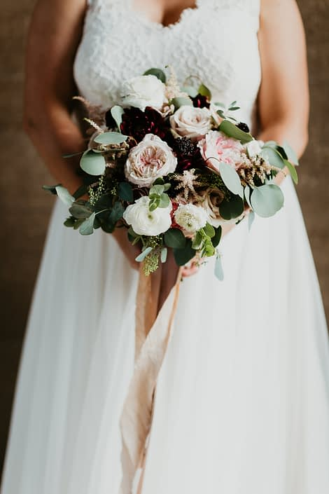Bridal bouquet featuring burgundy dahlias, Keira garden roses, white ranunculus, amnesia roses, quicksand roses, blackberry scoop scabiosa, light pink astilbe and a mixed variety of eucalyptus greenery finished with trailing ribbons.