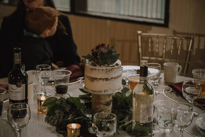 wedding cake centerpiece creathed with a naked cake on a birch log with a ring of eucalyptus greenery below and accented by a burgundy hearts garden rose and navy eryngium bloom