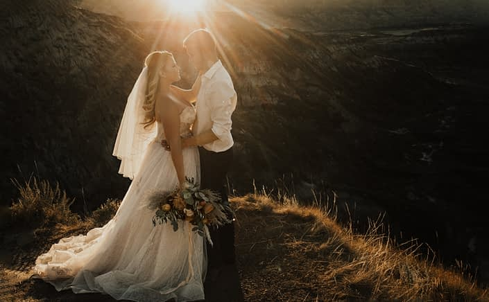 Boho Bride and groom with bouquet in Drumheller at sunset