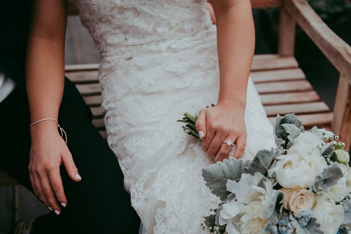 Bride's wedding ring and bridal bouquet with white peony and ivory roses