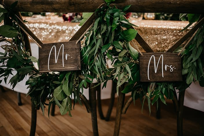 Rustic Boho Chic Wedding - Mr and Mr signs hanging from chair backs draped with garlands made of greenery.