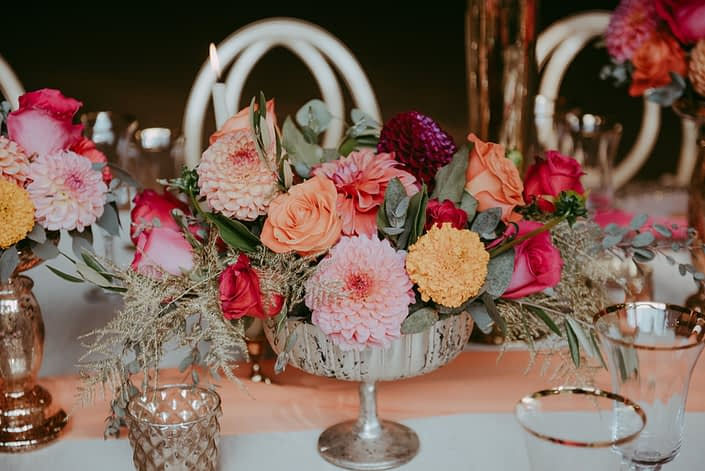 Bold fuchsia and orange compote arrangement with gold accents designed with roses, dahlias and zinnias