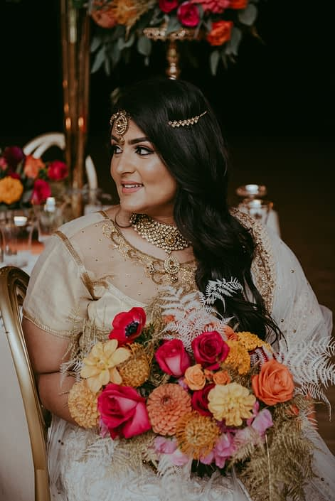 Bride with bold fuchsia and orange bridal bouquet with gold accents designed with anemones, roses, dahlias, sweet peas, zinnias, bleached bracken fern and plumosa