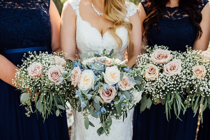 Bride and bridesmaids bouquets featuring quicksand roses, white o'hara garden roses, blue delphiniums, succulents, babies breath (gypsophila), and a mixed variety of eucalyptus greenery including feather, gunni, seeded and silver dollar.