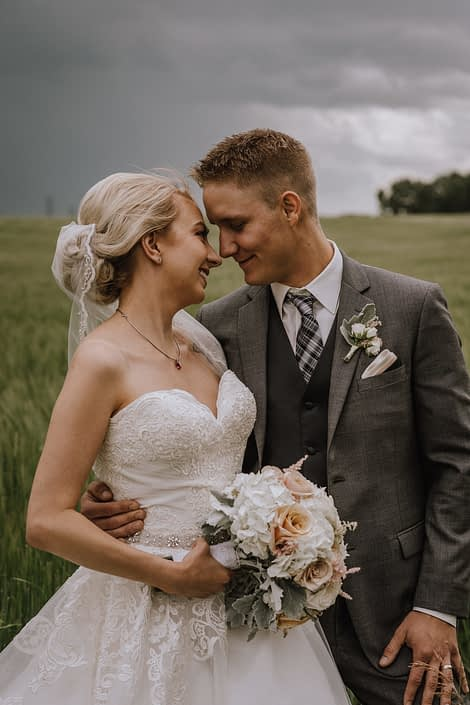bride and groom in stormy alberta weather in wheat field holding bridal bouquet of white hydrangea and blush rose and dusty miller bouquet
