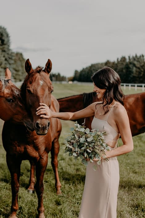 Erika' bridesmaid wearing mauve dress and holding a fresh mixed eucalyptus bouquet and petting a horse.