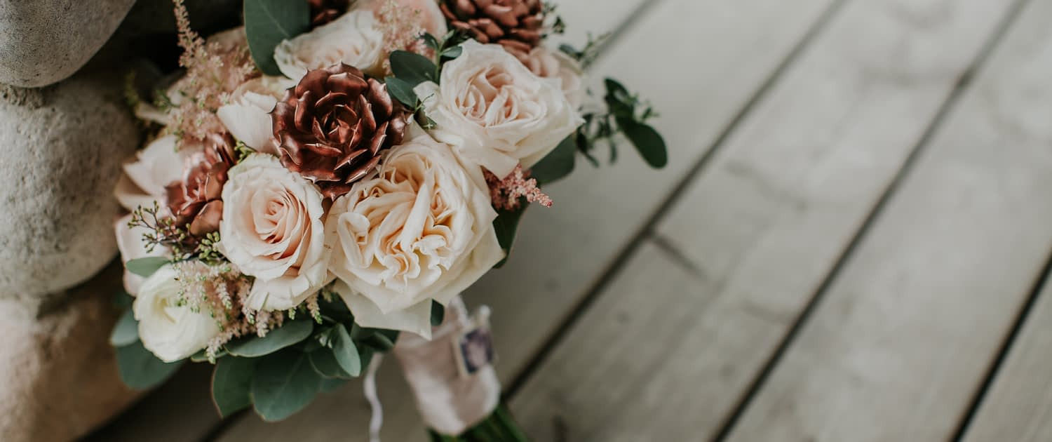 Close up detail shot of compact bridal bouquet made with white ohara garden roses and blush quicksand roses and astilbe and eucalyptus and rose gold succulents with brides photograph on the handle