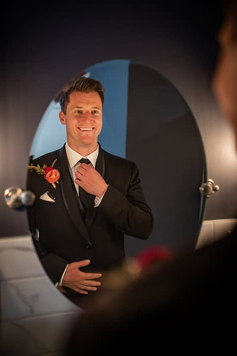 groom in grooms room at hilltop wedding center in black tux with coral and burgundy boutonierre