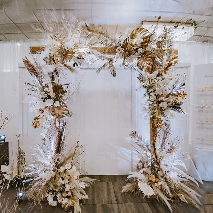 Down the Aisle Wedding Show 2020 wooden archway decorated with gold metallic painted monstera leaves, pampas grass, playa Blanca roses, Japanese white sweet peas, quicksand roses, painted Sago palm, and dried foraged grasses and branches.