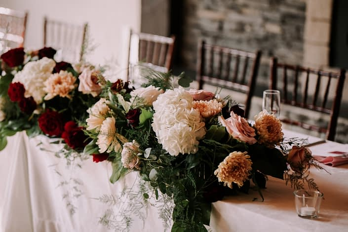 Rustic chic burgundy and blush head table arrangement featuring chrysanthemums, hydrangea and roses.