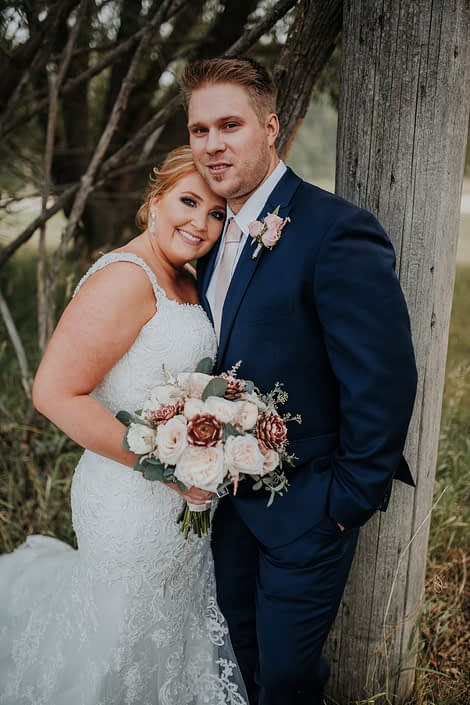 bride in white dress and groom in navy suit holding a bridal bouquet made with rose gold succulents and ivory garden roses and eucalyptus and boutonierre