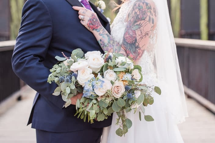 Bride and groom embracing white holding pink and blue bridal bouquet made of white o'hara garden roses, quicksand roses, ranunculus, delphinium, eryngium, astilbe, peach chrysanthemums and eucalyptus.